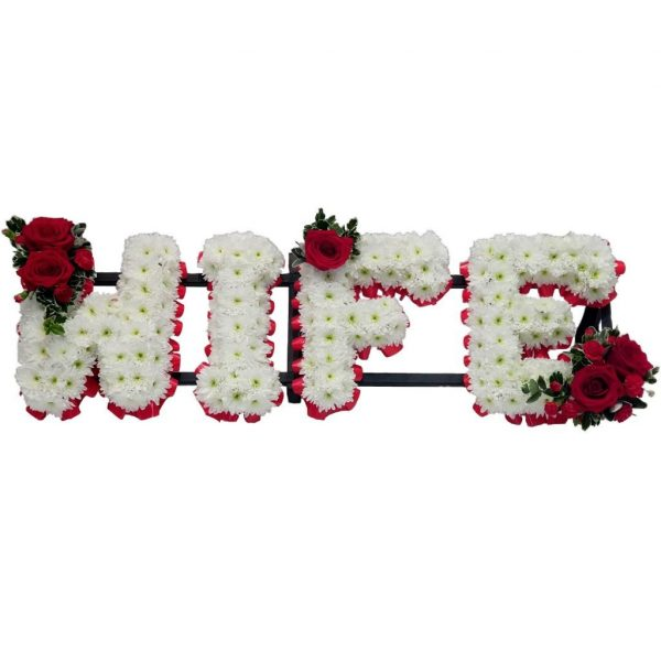 Wife Funeral Tribute – A white Chrysanthemum base bordered by Red Ribbon with a spray of Red Roses & baby Red Carnations.